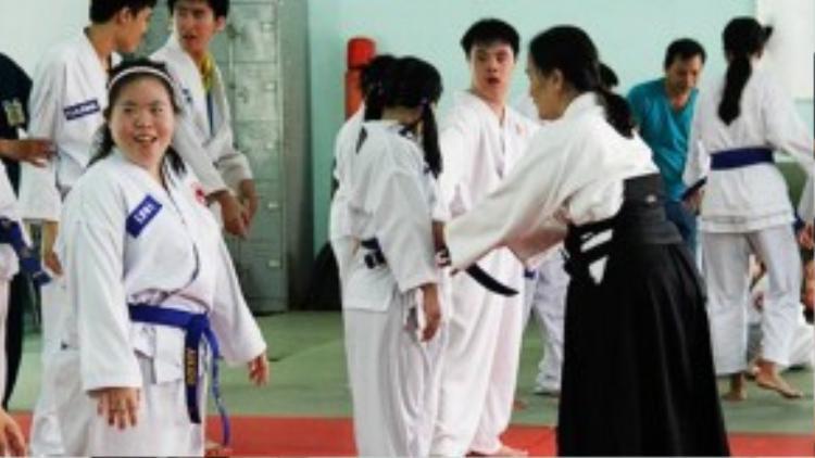 Cô chỉnh trang phục cho từng học viên của mình trước giờ học.