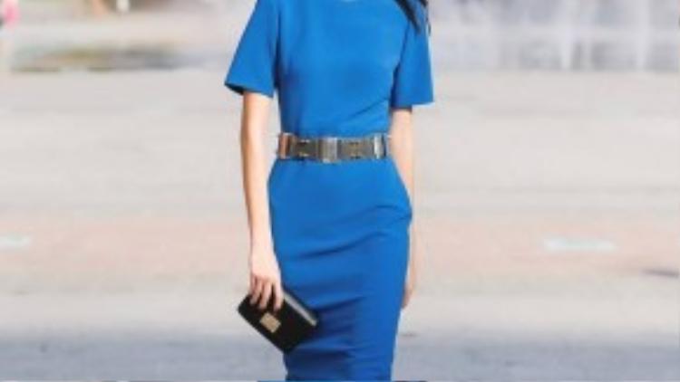 TyhD là một người mẫu có phong cách ấn tượng. Chiếc đầm xanh colbat được cô nhấn nhá bằng thắt lưng kim loại nổi bật. Chiếc ví cầm tay được thiết kế tối giản làm tăng vẻ sang trọng cho bộ trang phục.