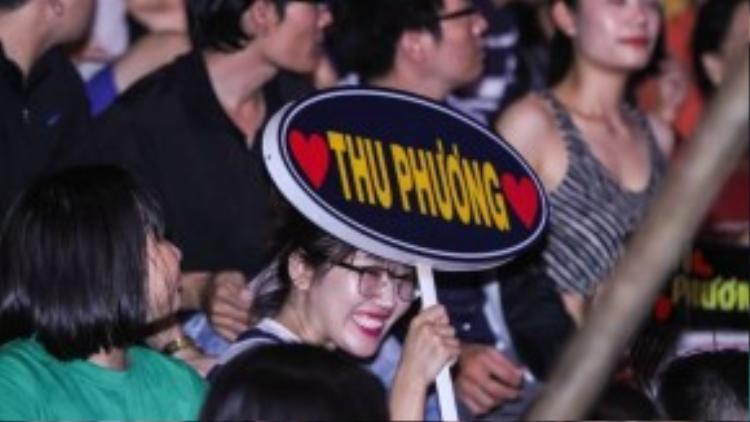Nụ cười rạng rỡ của một fan nữ khi trên tay cầm bảng cổ vũ ghi tên thần tượng của mình.