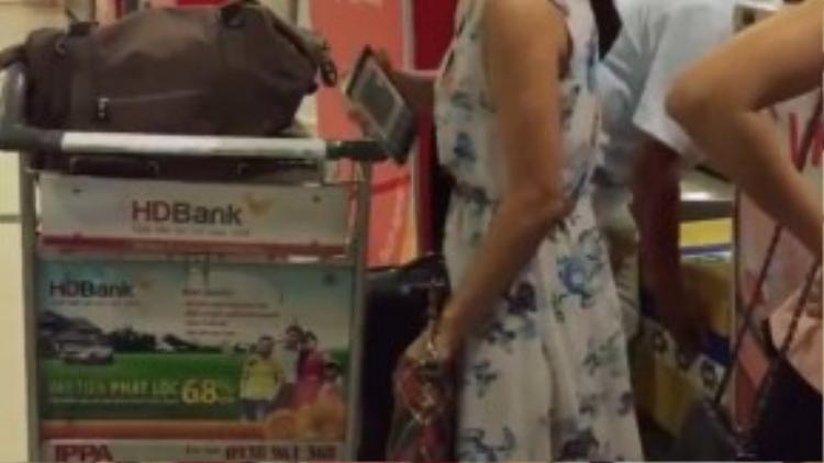 Người phụ nữ mặc váy hoa vừa làm thủ tục check-in với người đàn ông đi cùng, vừa luôn miệng chửi. (Ảnh chụp từ clip)
