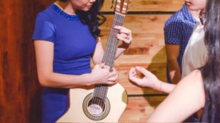Nữ HLV chu đáo kiểm tra âm thanh của đàn guitar trước khi luyện tập.