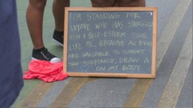 """Cô viết trên tấm bảng như sau: """"Tôi đứng lên cho những người đang phải đấu tranh với vấn đề tự trọng giống như mình, bởi vìmọi cơ thể đều là vô giá. Để ủng hộ cho việc chấp nhận chính bản thân mình, các bạn hãy vẽ một hình trái tim lên người tôi"""". (Nguồn: Ảnh chụp từ clip)"""
