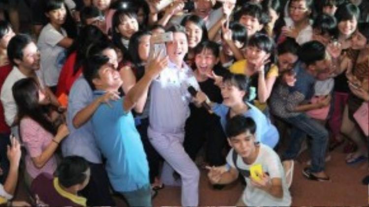 Đàm Vĩnh Hưng chụp ảnh tự sướng cùng các bạn trẻ trong lúc chờ nhạc dạo.