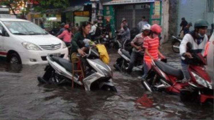Một bà mẹ đang cố gắng đẩy xe trong biển nướctrên đường Nguyễn Xí (quận Bình Thạnh), còn đứa con nhỏ của chị thìđang ôm gối say giấc trên xe. Ảnh: Đức Phú.