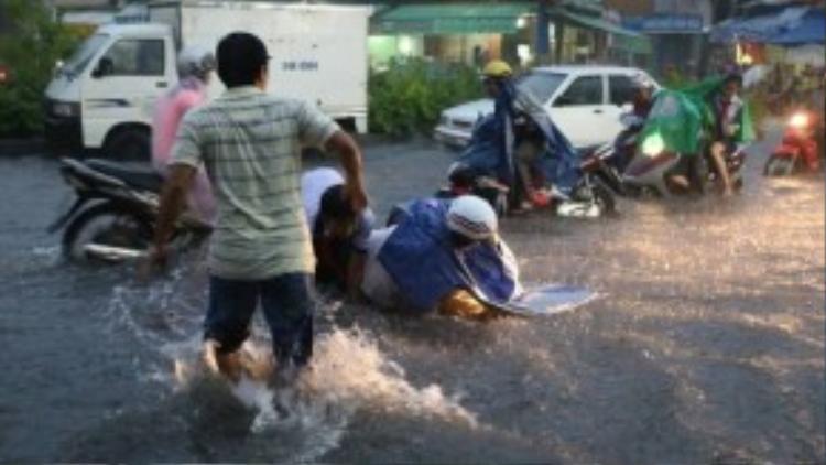 Điều khiển xe trong nước ngập sâu rất khó khăn, nhất là với các chị em phụ nữ tay lái yếu. Sóng nước mạnh do một chiếc ô tô chạy nhanh qua đã khiến nhiều xe máy loạng choạng và hai mẹ con trong ảnh té ngã sóng soài. Một người dân ở đó đã ngay lập tứclao ra giúp đỡ hai mẹ con. Ảnh: Quỷ Cốc Tử.