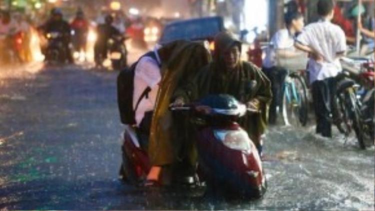 Một phụ huynh sợ con trai mình bị ướt nên quyết định đẩy xe cùng con mình ngồi trên đó dù cậu bé này cũng đã lớn phổng. Ảnh: Quỷ Cốc Tử.
