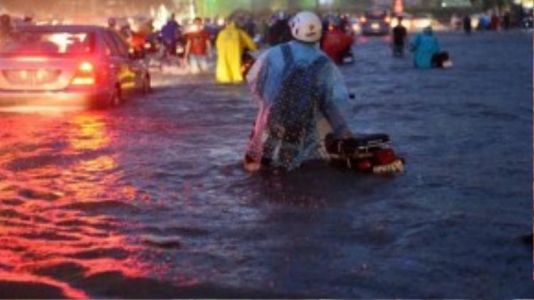 """Hầu như không có một chiếc xe máy nào có thể """"sống sót"""" qua biển nước với độ sâu hơn cả hồ bơi dành cho trẻ em này. Nhiều chủ phương tiện lường trước hậu quả đã chủ động tắt máy xe, dẫn bộ. Ảnh: Thuận Thắng."""