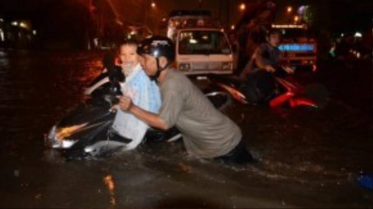 Một bé trai mặc áo mưa, ngồi trên xe và cười thật tươi trong khi người bố ướt từ đầu đến chân đang vất vả đẩy xe qua khu vực ngập sâu trên đường Kinh Dương Vương (quận Bình Tân). Ảnh: Thanh Tùng.