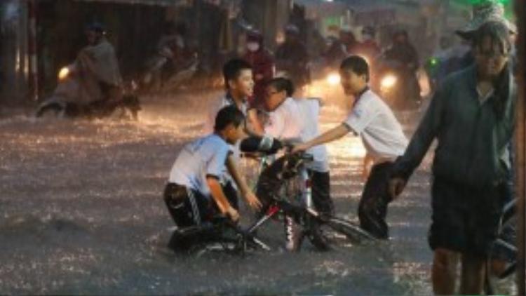 Các em học sinh trường THCS Lam Sơn dầm mưa, lội nước về nhà. (Ảnh: Zing.vn)