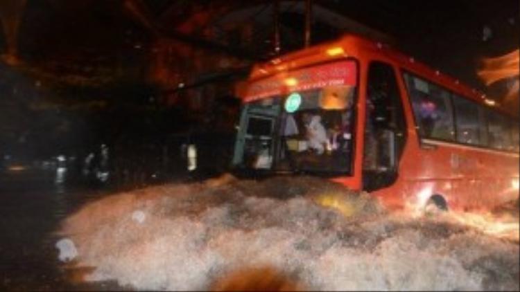 Xe Phương Trang chạy nhanh qua đường ngập tạo thành đợt sóng lớn đánh ngã các xe máy di chuyển trên đường Kinh Dương Vương (Q.Bình Tân) - Ảnh: Thanh Tùng