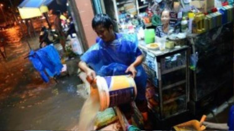 Anh Trần Hữu Nghĩa mệt nhọc tát nước ra khỏi nhà. (Ảnh: Thanh Tùng)