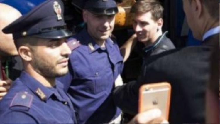 Cảnh sát Y bu quanh và tranh nhau chụp ảnh cùng Messi.