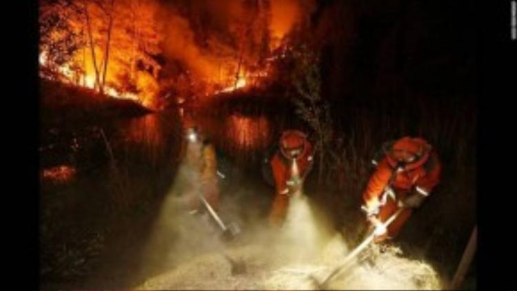 Ba lính cứu hỏa đang cố dập lửa ngăn chặn vụ cháy rừng tại thị trấn Middletown, California xảy ra vào ngày 13/09. Trận cháy lớn có tên Valley Fire đã thiêu rụi hàng trăm căn nhà chỉ trong một ngày Chủ Nhật.