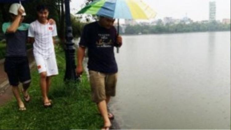 Hồ Đền Lừ, quận Hoàng Mai tại Hà Nội ngập nặng, nước tràn xung quanh khiến cua cá theo lên bờ. Người dân bất chấp mưa gió, tranh thủ đi bắt cá. (Ảnh: Vnexpress)