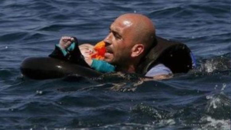 Một người đàn ông Syria đặt con trên chiếc phao cứu hộ sau khi chiếc xuồng cao su chở người tị nạn xì hơi khi chỉ còn cách bờ biển Hi Lạp 100m. Bức ảnh này tượng trưng cho những hiểm nguy mà người tị nạn phải đối mặt khi quyết định mạo hiểm băng qua Địa Trung Hải để tới Châu Âu. Cậu bé Aylan và em trai Galip cùng mẹ cũng đã thiệt mạng trong chuyến đi tới Hi Lạp vì xuồng cao su chở quá tải bị lật khi mới khởi hành không lâu. Cũng trong tuần vừa rồi, gần 40 người đã chết khi đang trên hành trình rời khỏi Thổ Nhĩ Kỳ tới đảo Lesbos, trong đó có 6 trẻ em, nạn nhân nhỏ nhất mới chỉ được 1 tuổi.