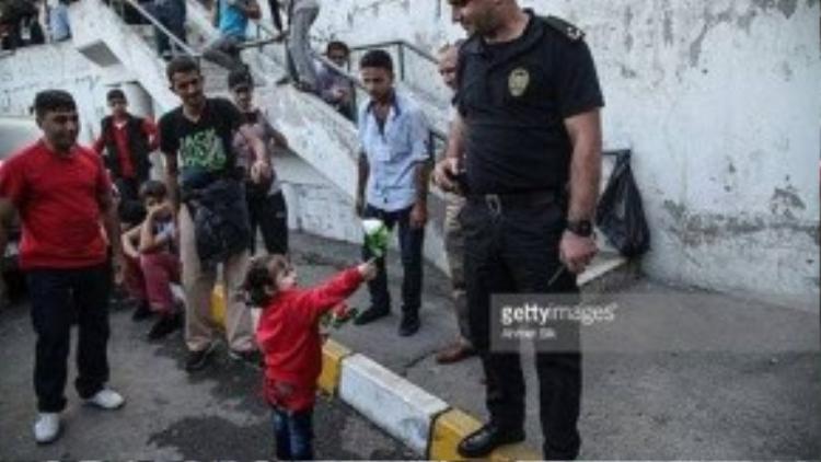 Một cô bé dân tị nạn trao bông hoa cho người cảnh sát Thổ Nhĩ Kỳ đang làm nhiệm vụ trấn áp dân tị nạn biểu tình vì phải đợi chờ quá nhiều ngày ở ga Esenler tại Istanbul. Hàng nghìn tị nạn buộc phải sống trong cảnh thiếu đồ ăn, thức uống và bệnh dịch sau khi chính phủ Thổ Nhĩ Kỳ ra quyết định không bán vé xe bus tới biên giới cho họ.