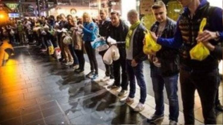 Các tình nguyện viên tại Frankfurt đứng xếp hàng để cung cấp thức ăn, nước uống và thiết yếu phẩm cho người tị nạn đến nước Đức. Ngay sau khi hình ảnh Aylan Kurdi nằm chết sấp mặt trên bãi biển Bodrum của Thổ Nhĩ Kỳ được công bố, thủ tướng Đức Angel Merkel đã thông báo tiếp nhận tất cả dân tị nạn Syria đến với nước này. Ảnh chụp sau khi hơn 10.000 tị dân đổ xô tới xin tị nạn ở Đức, người dân đã tình nguyện cung cấp thực phẩm và quần áo, giày dép, khăn quàng cho người tị nạn, thậm chí trẻ em còn được phát gấu bông miễn phí. Bà Merkel đã trở thành thần tượng trong lòng tất cả người dân Syria, nước Đức cũng được chọn để trở thành mái nhà thứ hai cho những con người khốn khổ này.
