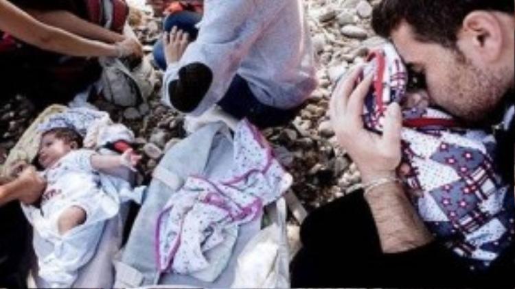Đây là một cặp sinh đôi 8 tháng tuổi người Syria, được bố mẹ đặt vào trong ba-lô mang theo trên chuyến hành trình băng qua biển Địa Trung Hải để tới đảo Lesbos, Hi Lạp. Bố mẹ của cặp sinh đôi đã mạo hiểm tính mạng của chính mình và cả hai đứa con, hi vọng an toàn vượt qua chuyến đi nguy hiểm để có một tương lai tốt đẹp hơn tại các nước Châu Âu trong khi quê nhà vẫn đang xảy ra cuộc nội chiến giữa phe chính phủ và lực lượng nổi loạn, nhà nước Hồi Giáo tự xưng IS. Mỗi chuyến đi của người tị nạn đều là một canh bạc cuộc đời, cửa sống thì ít, cửa chết lại quá nhiều. Tuy nhiên, đối với họ, thà đặt cược tính mạng để các con mình có một cuộc sống yên bình, hạnh phúc, không phải ngày ngày nơm nớp lo sợ sẽ có một quả bom rơi xuống, hay bị trúng đạn trong các cuộc giao tranh; thà một lần vượt qua cửa tử, còn hơn mỗi ngày đều phải đối diện với tử thần.