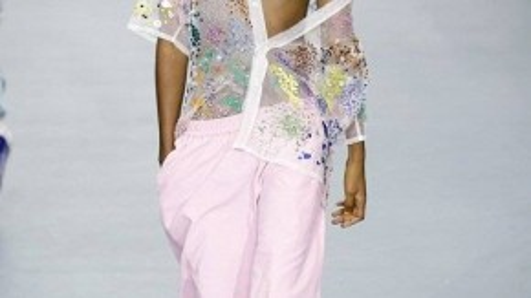 Một thiết kế áo sơ mi xuyên thấu được người mẫu nam thể hiện với giày đính kim sa màu hồng.