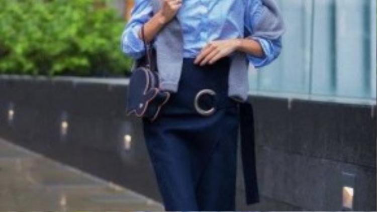Alexa Chung trang nhã trong set đồ màu xanh mát mắt cùng giày da mũi nhọn trước thềm show diễn của Christopher Kane. Cô tạo điểm nhấn bằng chiếc áo len màu xám quàng qua vai nữ tính.