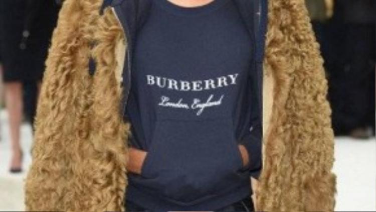 Siêu mẫu Jourdan Dunn sành điệu với chân váy cùng giày hở ngón da đen, khoác ngoài chiếc áo lông xù màu vàng nâu độc đáo tại show diễn của thương hiệu Burberry.