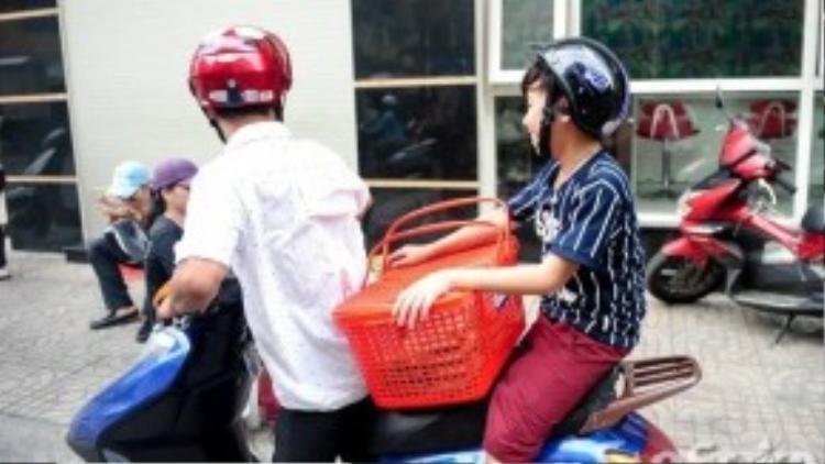 """Nhân tố tiềm năng của đội """"chị Tư"""" xếp bánh vào giỏ và cùng ba đi giao hàng bằng xe máy. Ba Công Quốc làm nghề sửa chửa điện song mỗi ngày anh luôn tranh thủ thời gian đưa đón vợ, đồng thời phụ một số việc lặt vặt."""