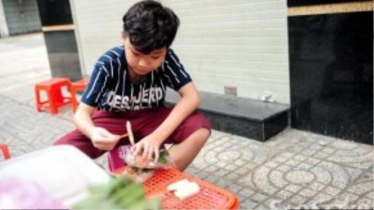 Thí sinh 12 tuổi gốc Phan Thiết giúp mẹ chất hàng ra bàn và tự tay bỏ từng chiếc chả vào các hộp bánh đang làm dang dở.