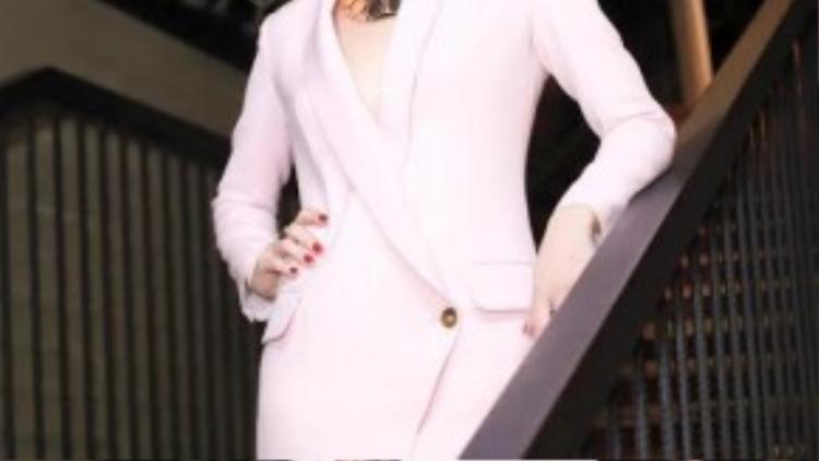 """Tham dự buổi họp báo chương trình Giọng hát Việt 2015, nữ ca sĩ xuất hiện trong chiếc váy dáng vest màu hồng pastel đơn sắc hợp mốt với vạt chéo phá cách tạo điểm nhấn. Thật sự Mỹ Tâm không thuộc về những gì rườm rà, diêm dúa. Cứ """"đơn giản đỉnh cao"""" như vậy là hợp với con người cô nhất."""