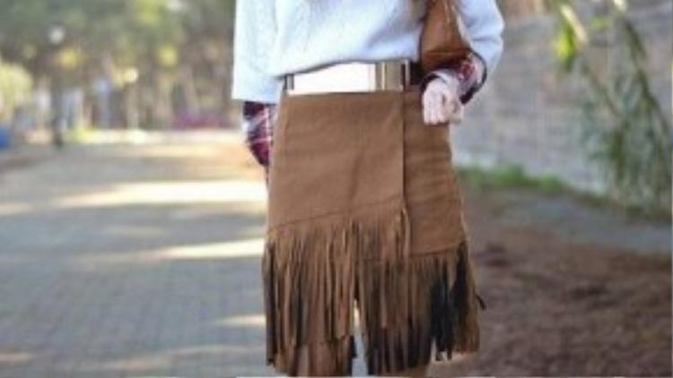 """Chân váy da lộn tua rua là một nét mới mẻ trong xu hướng năm nay. Kiểu váy suông vừa với chi tiết thắt lưng kim loại tạo điểm nhấn ngay """"vòng 2"""" là một set đồ khá tôn dáng."""