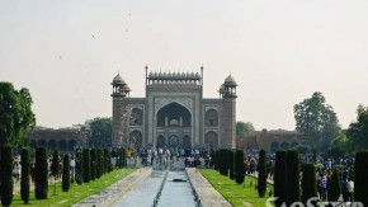 Bước qua cánh cổng vào đền là một thế giới khác, nó được hòa trộn bởi hoa, nắng và tiếng chim thánh thót. Du khách sẽ đi bộ khoảng 1km từ cổng chính để đến được khu vực lăng mộ chính. Taj Mahal luôn đông khách đến thăm, nên đôi lúc bạn sẽ cảm thấy thật nhỏ bé khi đi giữa dòng người tấp nập, nhưng chắc chắn nó sẽ làm bạn khó quên.