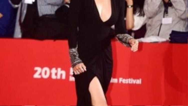 """Khác với phong cách an toàn thường thấy, """"nữ hoàng Ki"""" diện bộ đầm đen xẻ ngực sâu, bên dưới xẻ tà khá cao. Bộ cánh mang đến vẻ gợi cảm hiếm thấy ở Ha Ji Won. Nữ diễn viên cười rạng rỡ khi thu hút nhiều ống kính hướng về."""