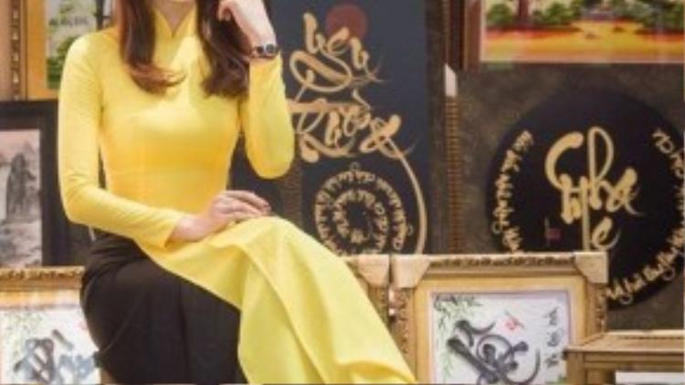 Kim Nhã thướt tha trong chiếc áo dài với mái tóc dài nhuộm tông sáng hợp với màu áo vàng chanh.