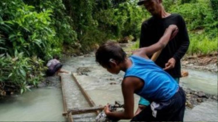 Một cậu bé đang đãi vàng tại mỏ Malaya, Camarines Norte, Philippines.