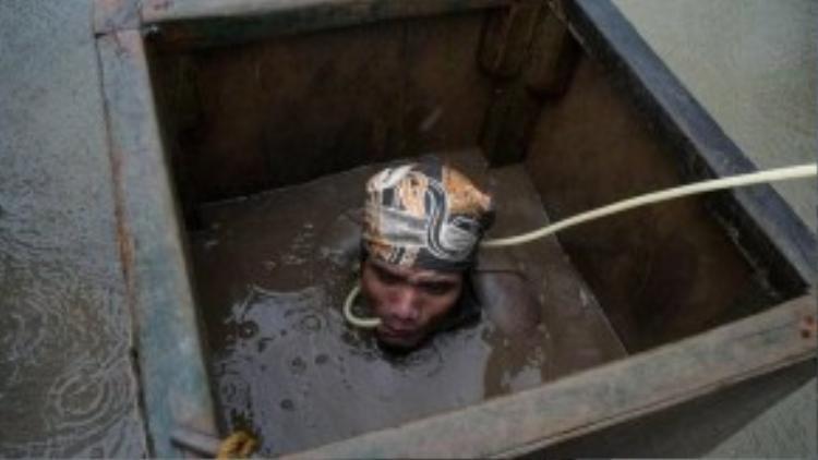 Người đào vàng lặn sâu xuống nước để đào bới, được trang bị 1 ống thở dài nối với bình ô-xy trên mặt nước.