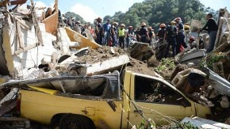 Một chiếc xe bẹp rúm ró dưới lớp đất đá. Đội cứu hộ đang cố gắng tìm kiếm những người bị mất tích.