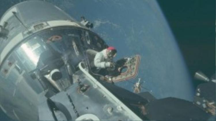 Một phi hành gia ở lối ra vào tàu Apollo 9 đưa thiết bị camera đặc biệt ra ngoài để chụp lại những bức ảnh độ phân giải cực cao cho chất lượng hình ảnh chính xác đến từng chi tiết. Góc chụp cho thấy phía sau lưng anh là đường cong mềm mại của hành tinh xanh Trái đất.