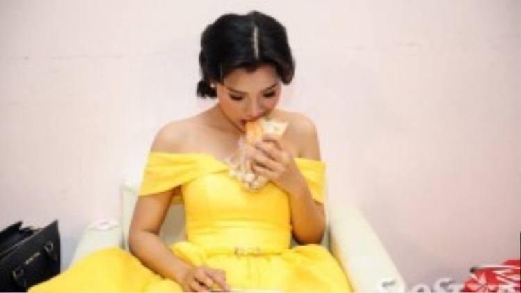 MC Hoàng Oanh ăn vội ổ bánh mì trong lúc xem lại kịch bản chương trình.