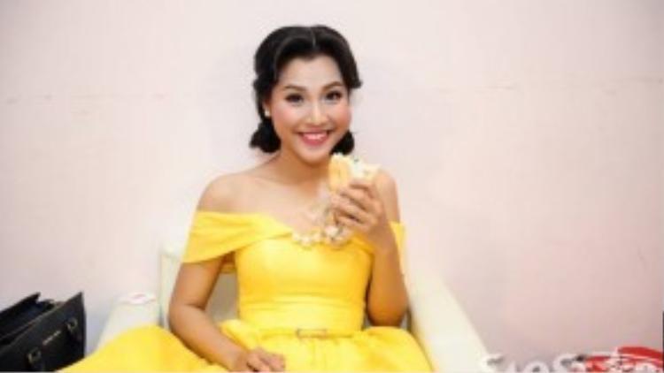 Bạn gái ca sĩ - diễn viên Huỳnh Anh cười tươi khi bắt gặp ống kinh máy ảnh hướng về mình.