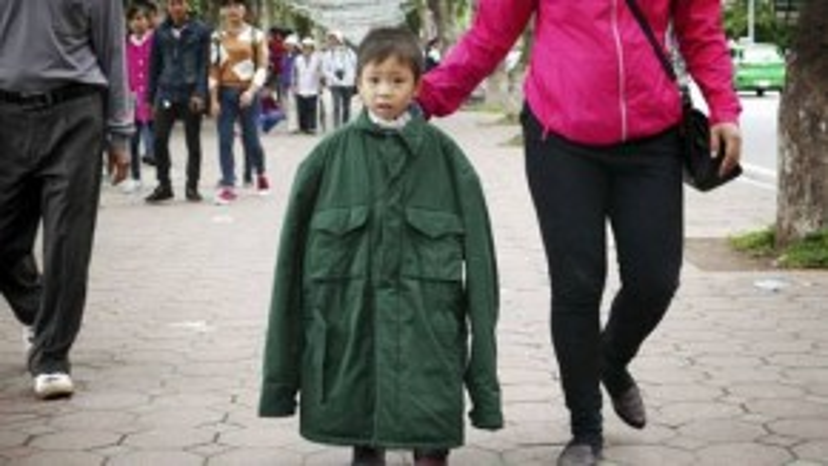 Do không chuẩn bị áo ấm, cháu bé phải khoác áo người lớn khi đi dạo cùng mẹ trên hè phố.