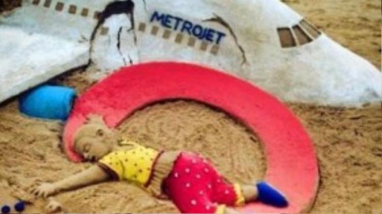 Nhà điêu khắc người Ấn Độ Patnaik đã làm mô hình thân máy bay từ cát, mô tả thi thể em bé nằm trên đất và một dấu hỏi màu đỏ để chia buồn với gia đình các nạn nhân thiệt mạng trong vụ tai nạn máy bay. Ảnh Lifenews.