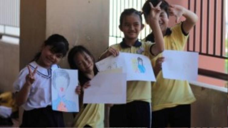 Các em nhỏ ở trường Hy vọng vui sướng khi cầm trên tay những bức tranh được các anh chị tình nguyện viên vẽ theo yêu cầu.
