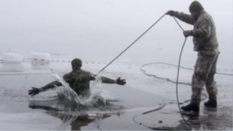 Một người lính Canada tập bơi ngay trong hồ băng tại Latvia, đây là một phần chương trình huấn luyện khắc nghiệt của NATO.