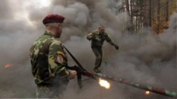 """Tại Belarus, các binh sỹ phải vượt qua thử thách khó khăn và khắc nghiệt trong điều kiện khói đạn mịt mù - một phần trong quy trình tuyển chọn để trở thành một đặc công trong binh đoàn """"Mũ nồi đỏ"""" danh giá."""