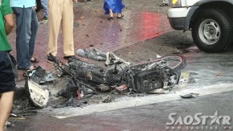 Một chiếc xe máy bị tông văng vào lề đường và bốc cháy được người dân dập tắt.