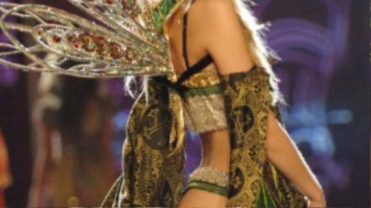 Caroline Trentini đẹp lộng lẫy như một nàng tiên trong show diễn 2005 với nhiều lớp vải được xếp tỉ mỉ cùng đôi cánh kim loại đính đá sang trọng, cuốn hút. Mặc dù rất nhiều màu sắc khác nhau nhưng tổng thể lại vô cùng hài hòa và ấn tượng.