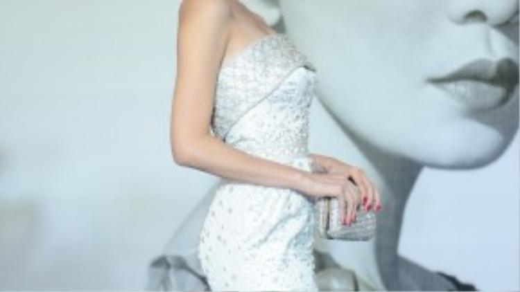 Ngọc Trinh duyên dáng đầm quây của stylist Đỗ Long, kết hợp cùng ví Alexander Queen.