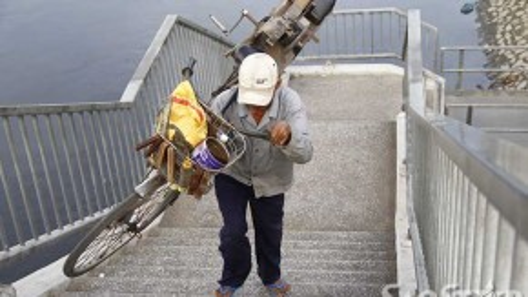 Nhiều người dân lao động mưu sinh bằng xe đạp vất vả vác xe qua cầu. Trong ảnh, chú Tân là nghề mài dao đang vác xe từ quận 8 lên cầu đi bộ số 5 để sang quận 5.