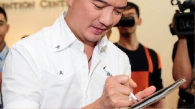 Đàm Vĩnh Hưng tất bật ký tặng album trước khi sự kiện bắt đầu.
