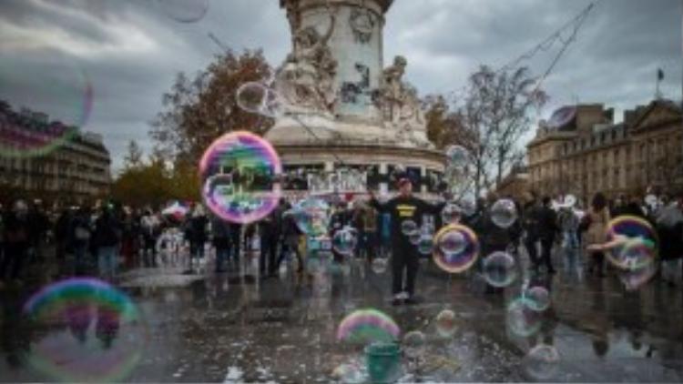 Một người đàn ông sử dụng que và dây để thổi bong bóng xà phòng tại Quảng trường Republiqué, nơi người Pháp mỗi ngày đều đến tưởng niệm các nạn nhân không may thiệt mạng trong vụ khủng bố Paris đêm 13/11.