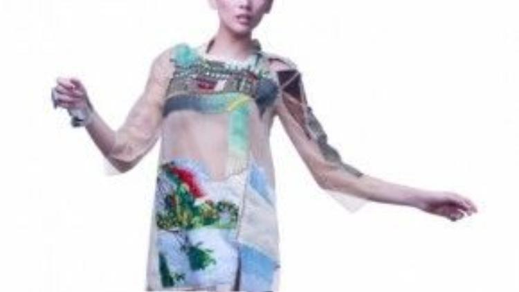 Siêu mẫu Hoàng Yến trong một thiết kế áo dài cách tân của Quảng Trọng Quang Nhật. Trên nền chất liệu see through trong suốt là những mảng màu được thêu và đính đá một cách khéo léo.